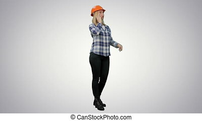 Beautiful female engineer in hardhat havin a phone call correcting the project on white background.