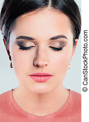 Beautiful female face closeup. Young woman with makeup, eyes closed