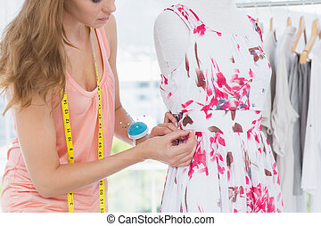 Beautiful female fashion designer working on floral dress