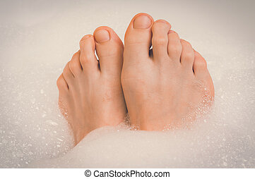 Beautiful female feet in bathtub with foam