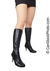 Beautiful female feet in black high boots