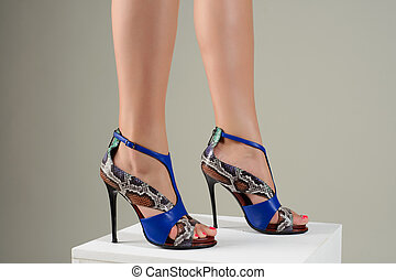 Beautiful female feet in stylish blue high-heeled sandals.