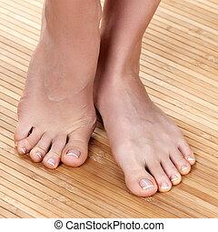 Beautiful female feet on a wooden floor, closeup shot