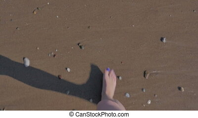 Beautiful female feet on the beach against the background of the sea, waves, foam, sand and pebbles. View from above. The concept of travel, tourism.