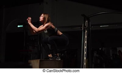 Beautiful female fitness athlete performs box jumps in a...