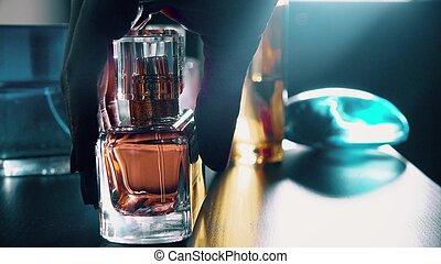 Beautiful female hand taking a bottle of perfume