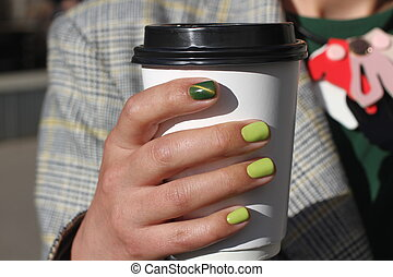 Beautiful female hand with manicure holds cardboard coffee cup. Tender yellow nail polish and green cat eye design.