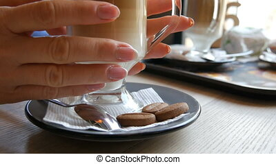 Beautiful female hands holding a glass with latte in cafe