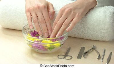 Beautiful female hands in aroma bath. Woman hands in glass...