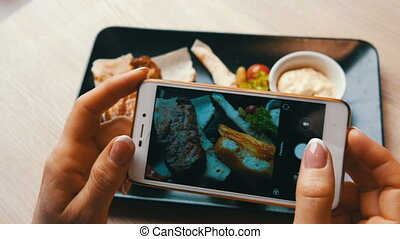 Beautiful female hands make food photo of a piece of juicy...