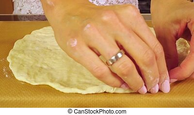 Beautiful female hands making edge of homemade pizza