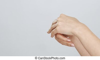 Beautiful female hands studio close-up. Arms of young woman applying cream. Anti-aging, healthcare and rejuvenation concept.