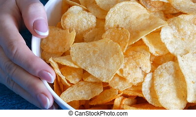 Beautiful female hands taking potato chips from huge plate,...