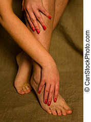 Beautiful female hands with a manicure are on their feet.