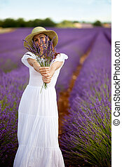 Beautiful female holding a bouquet of lavender twigs in both...