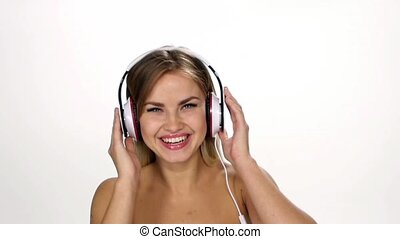 Beautiful female in headphones listening to the music with fluttering on the wind hair over white background. Slow motion.