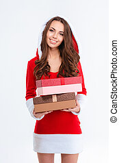 Beautiful female in santa claus costume standing with two gifts