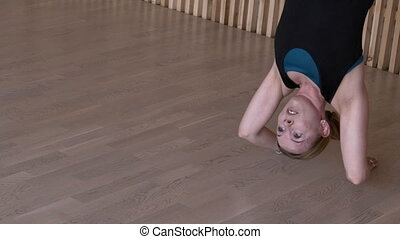 Beautiful female is hanging upside down sports club. Fitness...