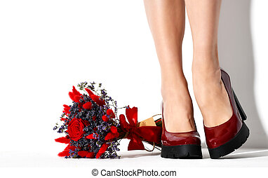 Beautiful female legs and bouquet of red blue flowers on white