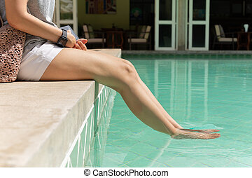Beautiful female legs in a pool vacation concept.