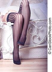 Beautiful female legs in fishnet stockings in bed