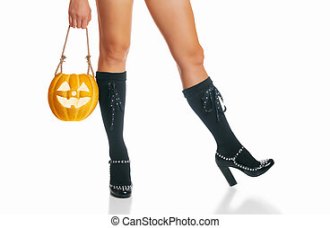 Beautiful female legs in shoes of witch and Halloween pumpkin.