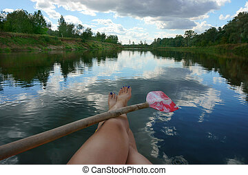 female legs in the river and paddle