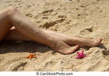Beautiful female legs on the beach