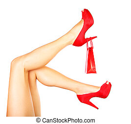 Beautiful female legs with red heels and shopping bag...