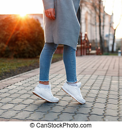 Legs With Tennis Shoes And Jeans On A White Backgroud