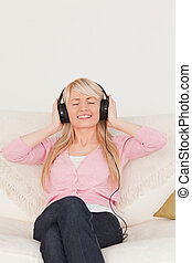 Beautiful female listening to music on her headphones while sitting on a sofa in the living room