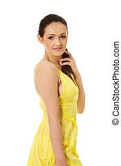 Beautiful female model in yellow dress.