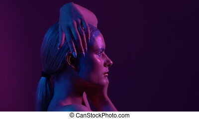 Attractive Female Blond Raises Hands Up to Head. Pink and Violet Studio Background. Left Side Profile Portreit.
