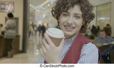 Beautiful female model with green eyes sipping from a cup smiling and looking at the camera in a mall coffee shop