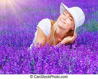 Beautiful female on lavender field - Pretty woman sitting on...