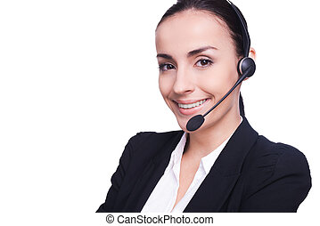Beautiful female operator. Confident young woman in headset smiling and keeping her arms crossed while standing isolated on white