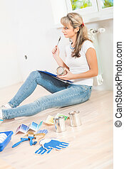 beautiful female painter sitting on the floor holding paint can