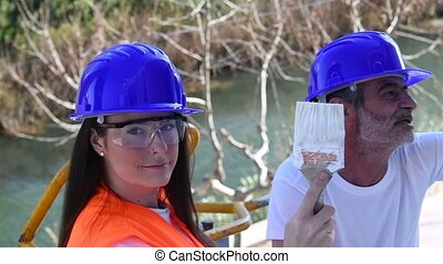 Beautiful female painter with safety gear looks at the camera and shows her paint covered brush in slow motion. Work concept.