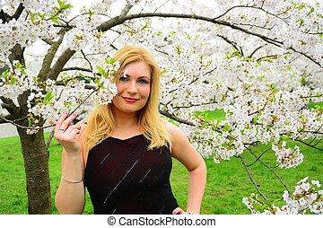 Beautiful female posing in the sakura garden