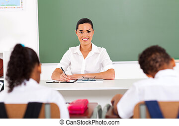 beautiful female primary school teacher sitting in classroom