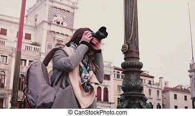 Beautiful female professional journalist with camera taking...