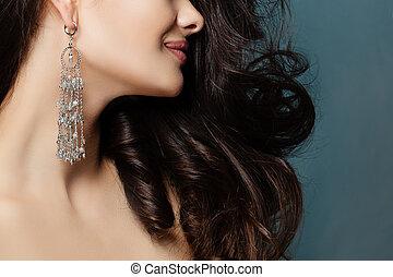 Beautiful female profile on blue background, close up portrait