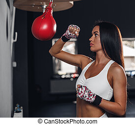 Beautiful female punching a boxing pear at the gym