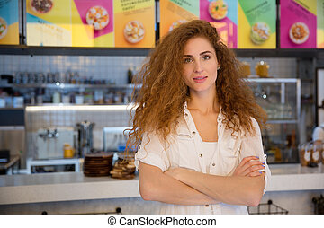 Beautiful female red haired barista looking at camera and smiling