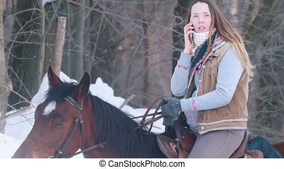 Beautiful female rider use phone in winter field, outdoor...