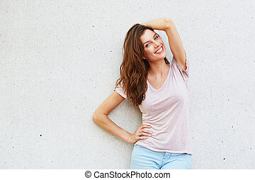 beautiful female smiling with hand in hair against white wall