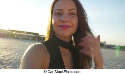 Beautiful female taking selfie on the beach