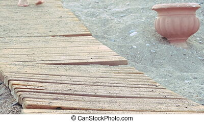 beautiful female tanned feet walking along wooden walkway on beach. girl walks on beach
