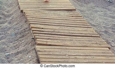 beautiful female tanned feet walking along wooden walkway on...