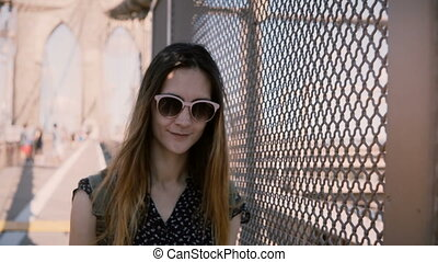 Beautiful female tourist in sunglasses smiling, leaning to...